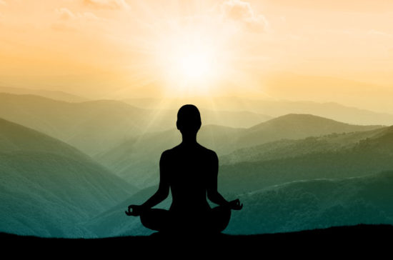Person mediterer på bjergtop - mærk efter og find ro